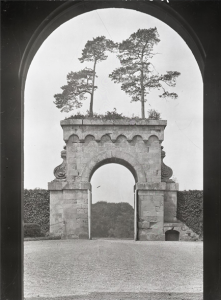 The great arch and its fantastic overgrowth seen from the entrance to Eastbury House. The trees are still there today. Country Life  03/09/1927
