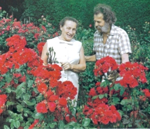 Dorothy and Harry standing behind a bed of Dorothy Wheatcroft roses, from My Life with Roses