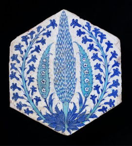Tile of fritware painted with blue and turquoise enamels. Hexagonal, and in one angle a blue and turquoise cypress grows from a cluster of blue leaves, flanked by notched turquoise leaves on which are white flowers in reserve, and by carving hyacinths.